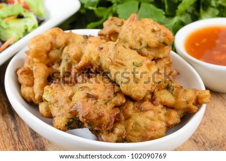 Vegetable Pakora or Onion Bhajis served with salad and chili sauce.