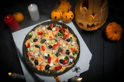 Vegetable pizza on delivery box near Halloween decoration. Scary pumpkins with painted faces, Lights of burning candles In horror smoke. Dark background with cobwebs and spiders near fast food dish