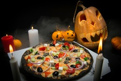 Vegetable pizza on takeaway box near Halloween decoration. Scary pumpkins with painted faces, Lights of burning candles In horror smoke. Dark background with cobwebs and spiders near fast food dish