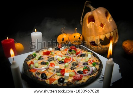 Vegetable pizza on takeaway box near Halloween decoration. Scary pumpkins with painted faces, Lights of burning candles In horror smoke. Dark background with cobwebs and spiders near fast food dish Imagine de stoc ©