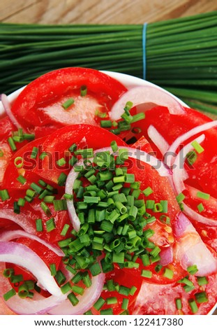vegetable salad : fresh tomato salad in white bowl with bundle of chives , tomatoes on twig , onion, over wooden table
