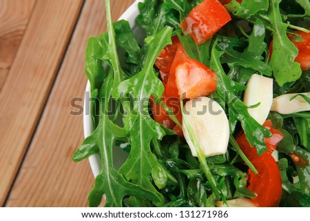 vegetable salad : green salad with raw tomato and garlic in white bowl over wood served with cutlery