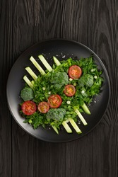 Vegetable salad on dark platter design haute cuisine. Photo in low key.
