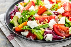 Vegetable salad plate with avocado, bell pepper, tomato, fresh lettuce, soft cheese and pine nuts. Healthy diet food.