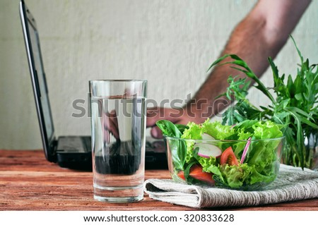Vegetable salad with a glass of pure water on the wooden table closeup. In the background, a man working with a laptop. The concept of people working outside the office and healthy lifestyle #320833628