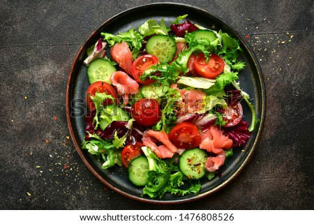 Vegetable salad with salmon and salad leaves mix on a plate on a dark slate, stone or concrete background. Top view with copy space.