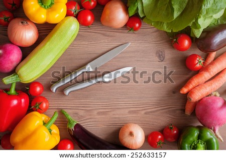 Vegetable set with knifes: ripe tomatoes, paprika, zucchini and an eggplant on a wooden background with a copy space in the center. Top view #252633157