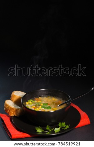 Vegetable soup in a black plate, on a dark background