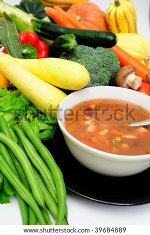 Vegetable soup in a bowl surrounded by fresh vegetables including squash, carrot, green beans, mushrooms, celery and bell peppers