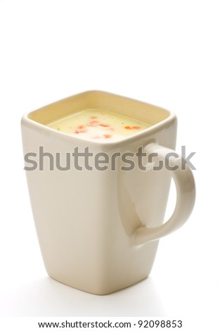 Vegetable soup in a square cup on white background.