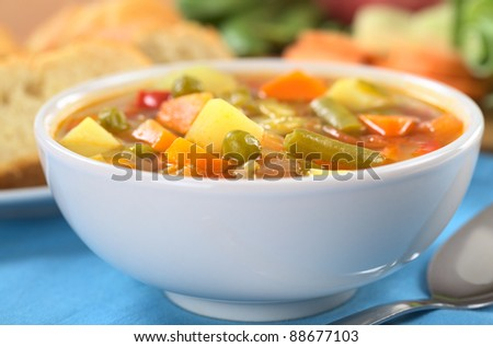 Vegetable soup made of green bean, pea, carrot, potato, red bell pepper, tomato and leek in white bowl (Selective Focus, Focus on the vegetables one third into the soup)