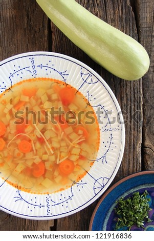 Vegetable soup next to fresh zucchini and chopped parsley. Rustic take on a wooden background.