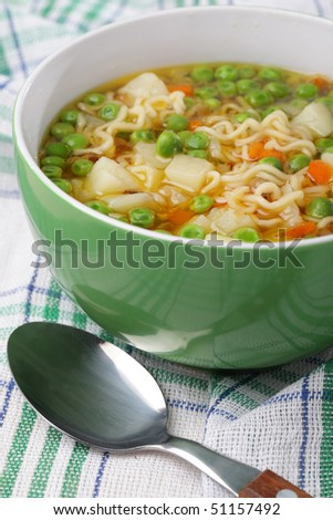 Vegetable soup with pasta in a green bowl - stock photo