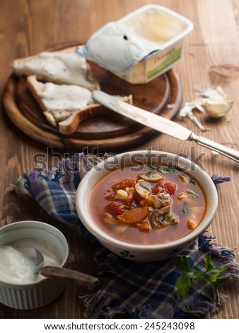 Vegetable soup with tomato on wooden background, selective focus