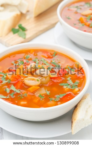 Vegetable soup with white beans in a bowl closeup on a white table vertical