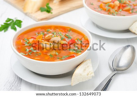 Vegetable soup with white beans in a bowl on a white table