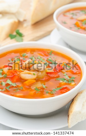 Vegetable soup with white beans in a bowl on a white table closeup