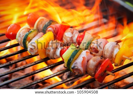 vegetable spit on grill flames in background