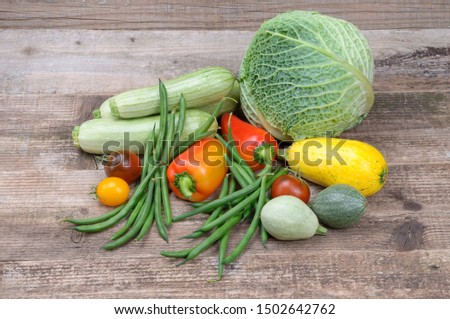 Vegetable still life. Head of savoy cabbage, tomatoes of different varieties and sweet pepper. String beans and zucchini of several types. On a wooden background.