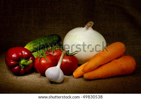 Vegetable still life with tomatoes, onion, bell pepper, cucumbers, carrots and garlic on burlap background