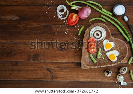 Vegetables and a plate with fried eggs in heart shape on wooden background overhead close up shoot #372681772