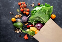 Vegetables and cereals in a paper bag on a black background. The concept of a consumer basket, online shopping, healthy food.