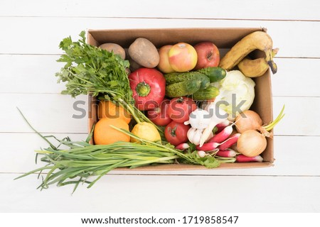 vegetables and fruits are in a cardboard box on a white wooden background. Flat Lay, Copy Space. Fruit storage box. Food delivery