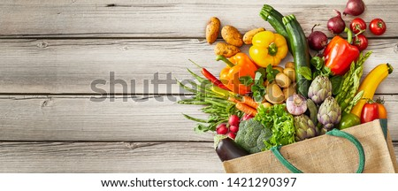 Vegetables and fruits falling out of tipped over bag next to large empty space over rustic wooden background #1421290397