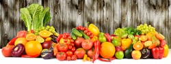 Vegetables and fruits on dark wooden wall background. Copy space
