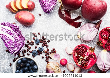 Vegetables and fruits with anthocyanin purple and pink: red cabbage, onion, pomegranate, blueberries, rice, apples, potatoes, garlic beans, radish for healthy nutrition. Top view. Color year violet #1009911013