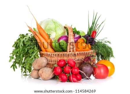 Vegetables and greens in a wattled basket on a white background