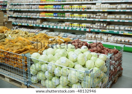 Vegetables and groceries in supermarket, focus is on cabbages - stock photo