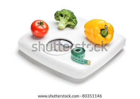 Vegetables and measuring tape on a weight scale isolated on white background
