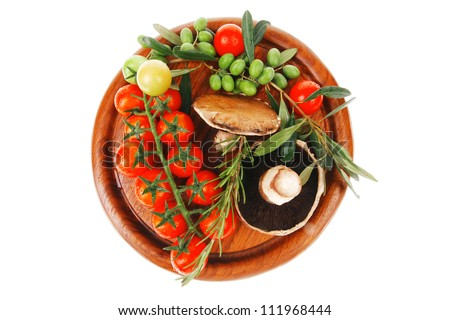 vegetables and olives over wooden plate on white