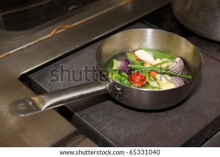 Vegetables are being boiled in pan on professional kitchen