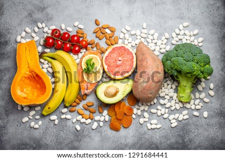 Vegetables, fruit and foods containing potassium over gray stone background, top view. Natural sources of potassium, vitamins and micronutrients for healthy balanced diet and avitaminosis prevention Stock fotó ©