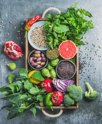 Vegetables, fruit, seeds, cereals, beans, spices, superfoods, herbs, condiment in wooden box for vegan, gluten free, allergy-friendly, clean eating or raw diet. Grey concrete background and top view