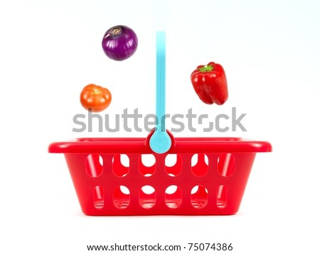 Vegetables going into a shopping basket isolated against a white background