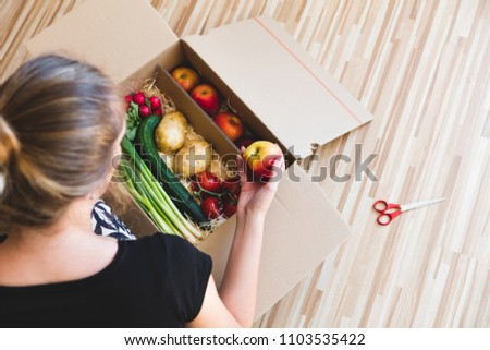 Vegetables grocery box, woman holding a apple, delivery box