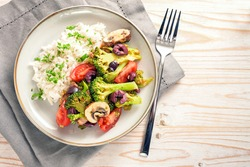 Vegetables like broccoli, tomatoes and olives with rice on a gray plate and a bright wooden table with napkin and fork, healthy vegetarian meal, copy space, high angle view from above, selected