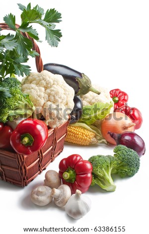 Vegetables. Mix of fresh ripe vegetables placed in a wicker basket and around isolated on white background