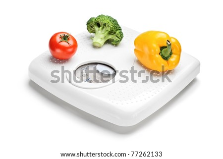 Vegetables on a weight scale isolated on white background
