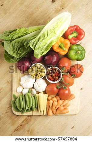 Vegetables on a wooden kitchen table, lit with a large light source from the right.