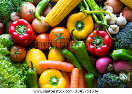 Vegetables on the black background. Organic foods and fresh vegetables. Cucumber, cabbage, pepper, salad, carrot, broccoli, lettuce and tomato on the table. #1345751834