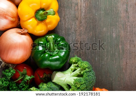 Vegetables on wood background with space for text. Farmers food. Bell pepper, onion, garlic, carrots and other vegetables.