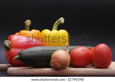 vegetables on wood chopping board  over dark grey background