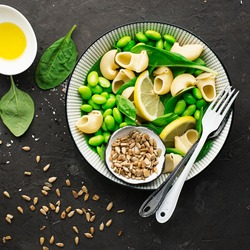 Vegetables, pasta, spinach, seeds bowl of salad. Vegetarian summer vegetable bowl with pasta and olive oil. Top View
