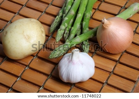 vegetables - potato, asparagus spears, brown onion and garlic on wooden kitchen mat #11748022