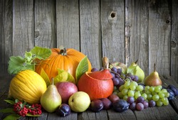 Vegetables pumpkins and fruits in autumn halloween season still life on vintage wooden boards