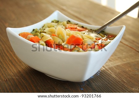 Vegetables soup with a spoon on a wooden table